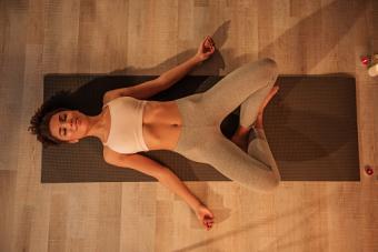 young woman doing yoga on mat