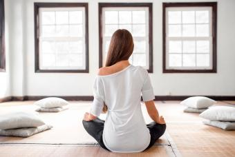 Seated woman practicing yoga indoors