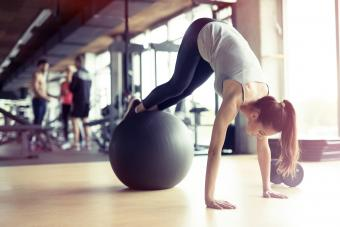 Athletic woman exercising with ball in gym