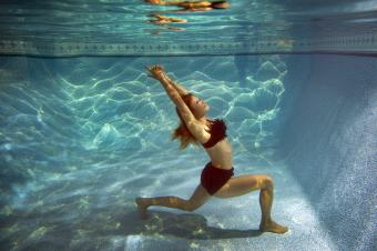 Woman doing yoga underwater in a swimming pool