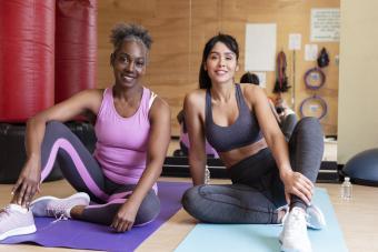 Smiling women sitting on yoga mats