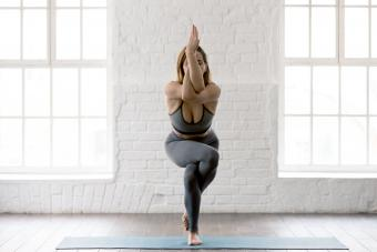 Woman practicing yoga, standing in Eagle pose