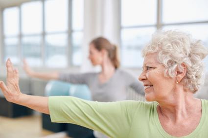 Elderly woman at yoga class