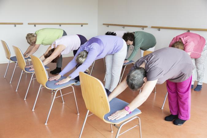 senior women yoga class with chairs
