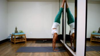 Woman achieving complete yoga handstand