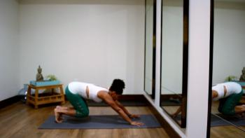 Woman getting into downward dog position