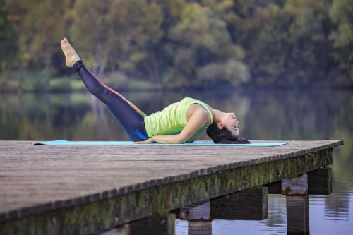 woman doing fish pose on a dock