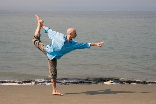 Man practicing yoga at beach