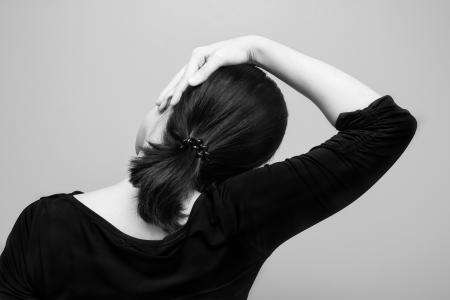 Rear view of woman stretching neck
