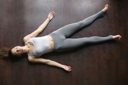 Woman doing yoga corpse pose