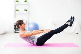 Woman doing Half-Boat pose on mat at home