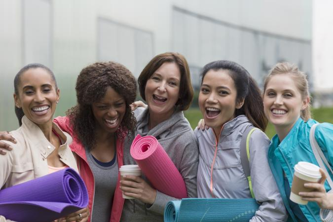 happy women with yoga mats