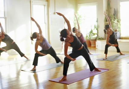 Group of women stretching in yoga class, arms raised