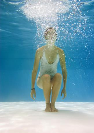 Teenage girl in pool doing the chair pose under water