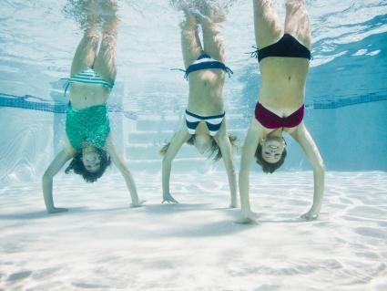 Teenagers in a swimming pool doing handstands under water