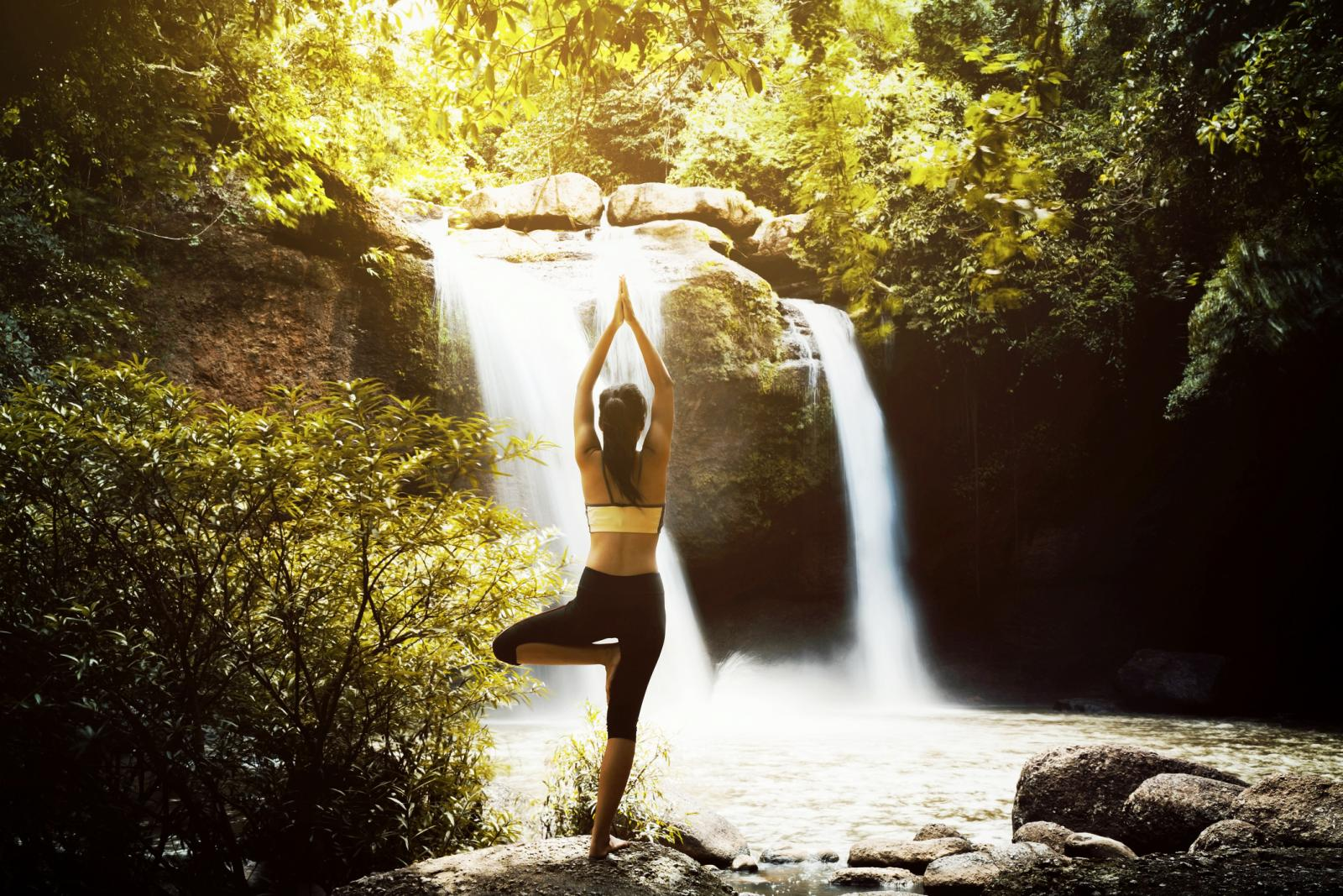 Woman Doing Tree Pose Yoga Against Waterfall