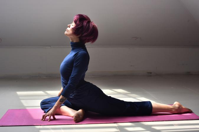 Woman doing half pigeon pose in yoga